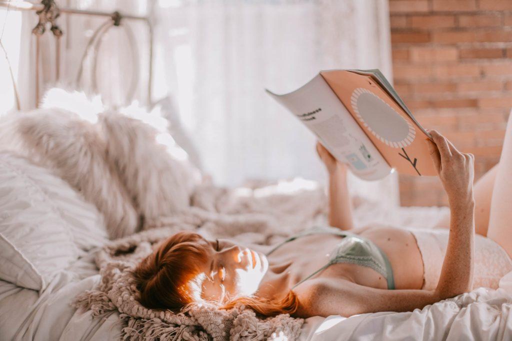 寝ながら本を読む女性